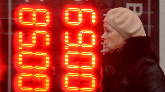 A woman walks past a board listing foreign currency rates against the Russian ruble outside an exchange office in Moscow on December 16, 2014.