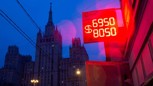 A neon sign displaying the latest Russian ruble euro dollar exchange rate in Moscow, Tuesday, Dec. 16, 2014.