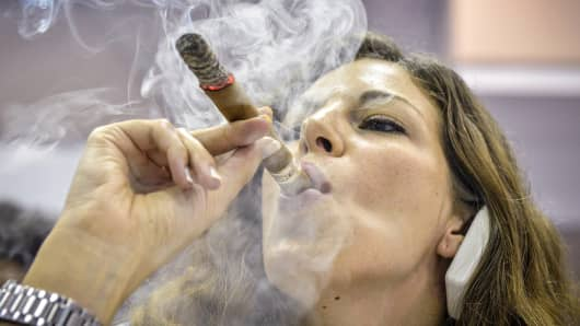A woman smokes a cigar during the XVI Havana Cigar Festival in Havana.