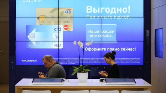 Customers use their mobile phones beside a digital advertisement inside a Citibank bank branch in Moscow.