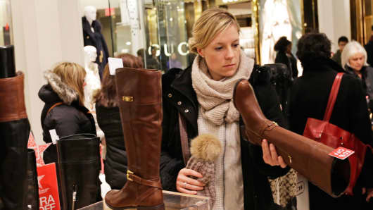 A customer looks at boots at a Macy's store in New York.