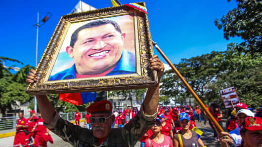 A man holds a portrait of late Venezuelan President Hugo Chavez as people gather on the streets of Caracas to commemorate 15 years of the adoption of the new Venezuelan Constitution, Dec. 15, 2014.