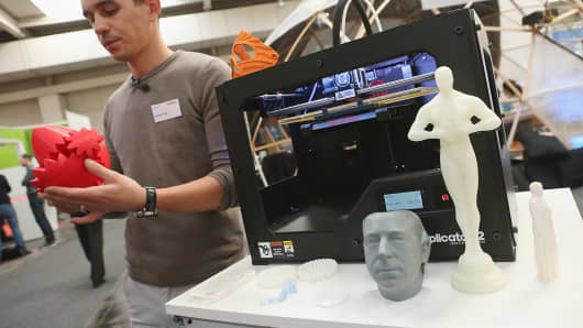 A host presents various objects created with a MakerBot 3-D printer at the CeBIT technology trade fair in Hanover, Germany.