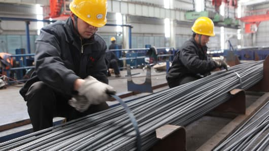 Two employees tie up steel bars at a steel-making plant in Ganyu, China.