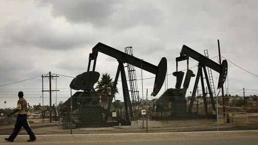 A pedestrian walks past pumpjacks operating at the Inglewood Oil field in Los Angeles.