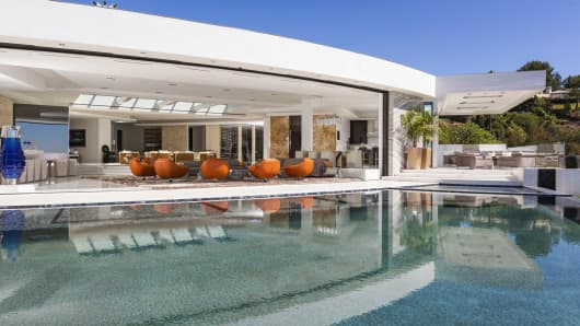 This Beverly Hills home features a 54-foot retractable wall of glass that opens out to the infinity pool.