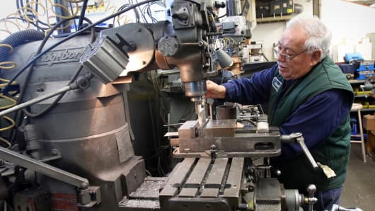 A worker making parts for industrial coffee grinding equipment at the Modern Process Equipment manufacturing facility in Chicago.