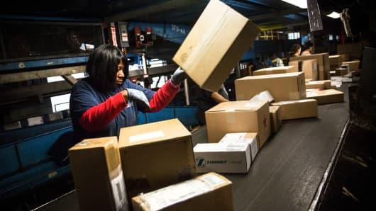 FedEx workers sort packages at a FedEx global hub.