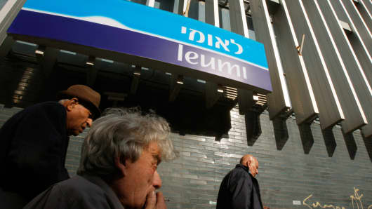 People walk by a branch of Bank Leumi.