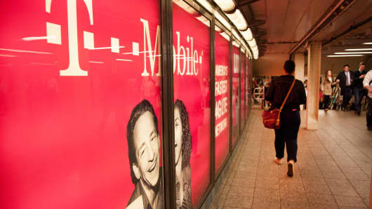 Pedestrians pass a T-Mobile ad in the New York City subway.