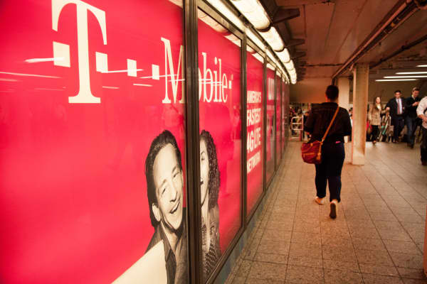 Pedestrians pass by a T-Mobile ad in the New York City subway.