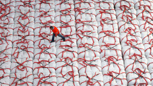 A longshoreman walks on bags of rice in a cargo ship at the Port of West Sacramento in California