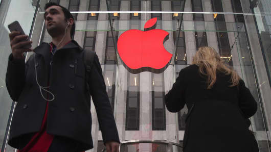 The Apple logo is illuminated in red at the Apple Store on 5th Avenue in New York.