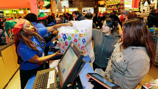 Employees assist shoppers at the check-out counter of a Toys R Us store in New York.