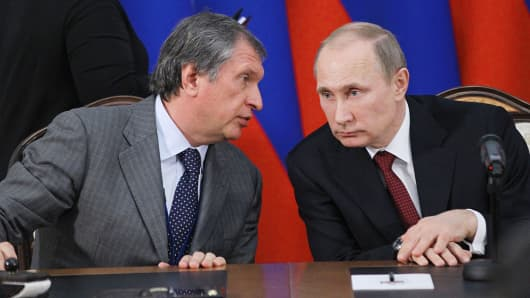 Russian President Vladimir Putin, right, listens to Igor Sechin, CEO of Rosneft.