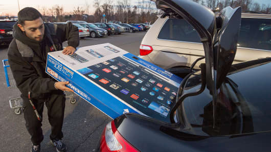 Umer Gonzalez loads his Samsung big screen TV in the trunk of his car after purchasing it at a Walmart in Fairfax, Va., Nov. 28, 2014.