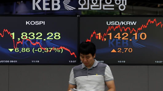 A foreign currency dealer stands in front of monitors at the Korea Exchange Bank headquarters in Seoul, South Korea.