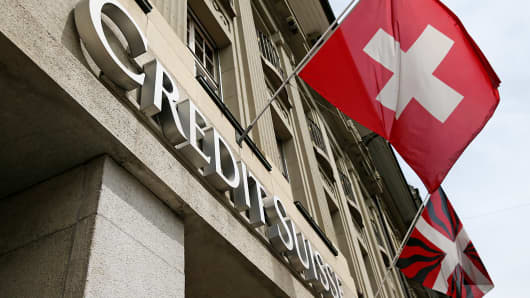The national flag of Switzerland flies above the entrance to a Credit Suisse bank branch in Bern, Switzerland, May 20, 2014.