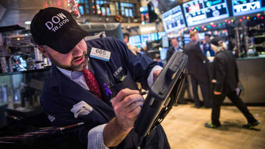 "Traders wear caps reading ""DOW 18,000"" as they work on the floor of the New York Stock Exchange, Dec. 23, 2014."
