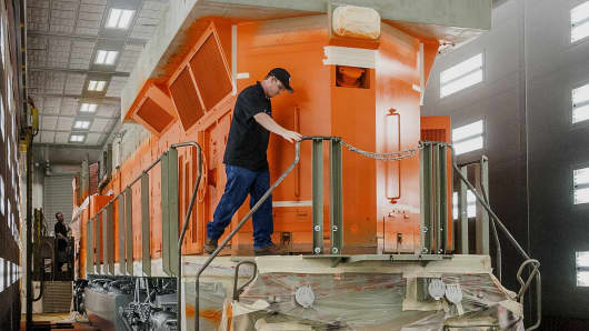 An employee preps a diesel locomotive for painting at the General Electric Manufacturing Solutions facility in Fort Worth, Texas.