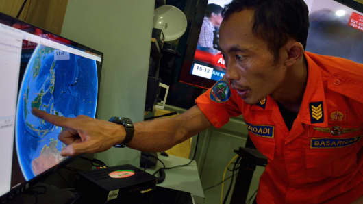 An official from Indonesia's national search and rescue agency in Medan, North Sumatra points at his computer screen to the position where AirAsia flight QZ8501 went missing off the waters of Indonesia.