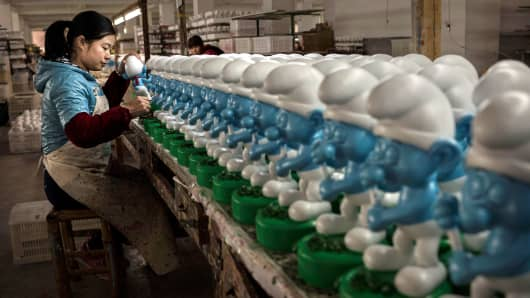 A Chinese worker paints unfinished licensed ceramic 'Smurfs' at the Shunmei Group (SMG) ceramics factory in Dehua,Fujian Province, China.