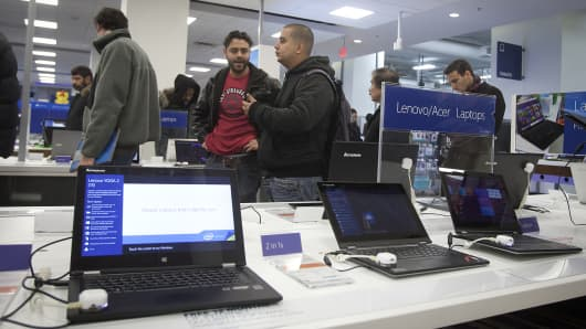 People line up near laptop computers to make their purchases at a Best Buy in New York.