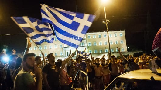 People wave Greek flags in front of the Greek Parliament.