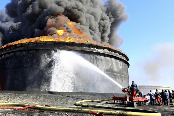 File photo of firefighters working to put out the fire of a storage oil tank at the port of Es Sider in Ras Lanuf. Oil tanks at Es Sider have been on fire for days after a rocket hit one of them, destroying more than two days of Libyan production