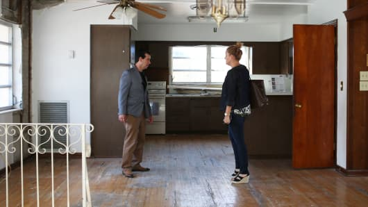A real estate agent, right, shows a home for sale to a home shopper in Miami.