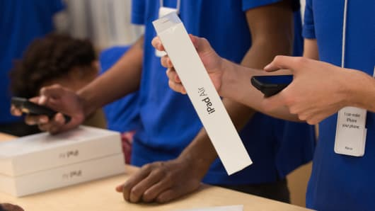 An Apple Inc. employee scans the price of an iPad Air at the 5th Avenue Apple store in New York.