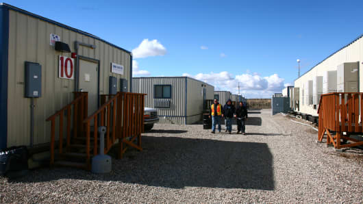 Workers walk the grounds a temporary worker housing site outside Williston, N.D.