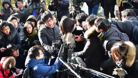 Cho Hyun-Ah (center), the daughter of Korean Air's chief executive, is surrounded by media upon her arrival for questioning at the prosecutors' office in Seoul on December 17, 2014.