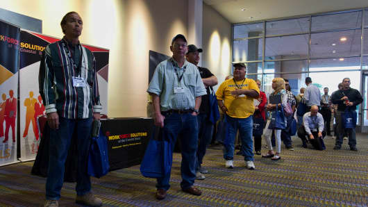 Job seekers wait in line to enter the Eagle Ford Shale Job Fair at the American Bank Center in Corpus Christi, Texas.