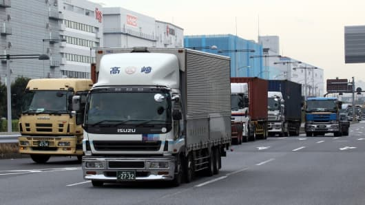 Trailer trucks are driven near the international cargo terminal to deliver containers at the port in Tokyo