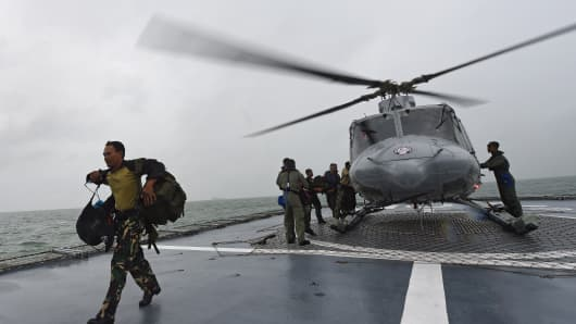 Officers arrive via helicopter on the Indonesian Navy vessel KRI Bung Tomo as it takes part in search operations on January 1, 2015 for victims and debris from AirAsia flight QZ8501.