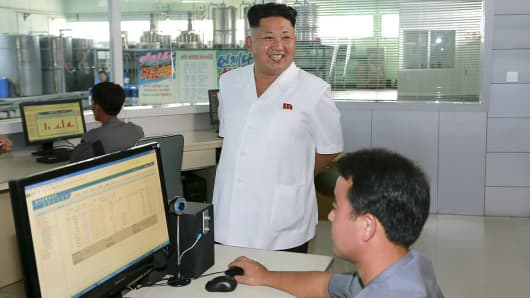 North Korean leader Kim Jong Un smiles during a visit to the Chonji Lubricant Factory, in this undated photo.