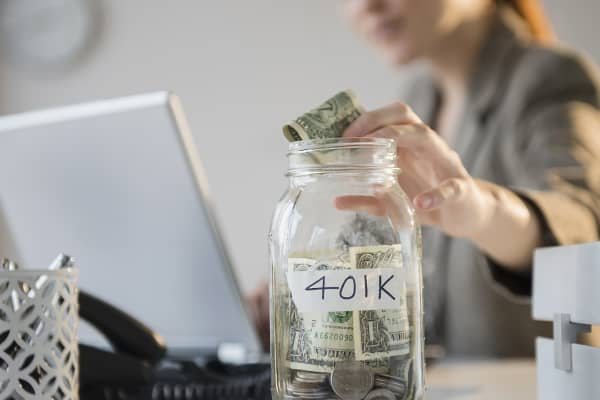 Businesswoman putting money into 401K jar at desk