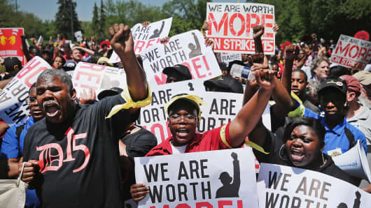 Fast food workers and activists demonstrate outside the McDonald's corporate campus, May 21, 2014, in Oak Brook, Ill.