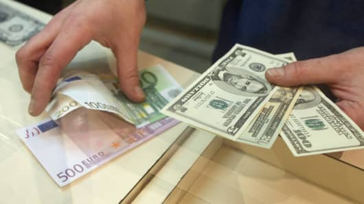 A clerk handles dollars and euros at a money exchange office in Paris.