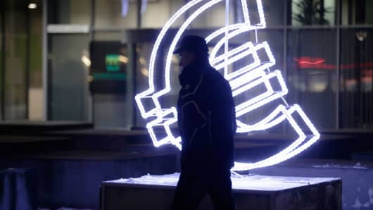 A man walks by a euro sign light installation in Vilnius, Lithuania, on December 31, 2014.