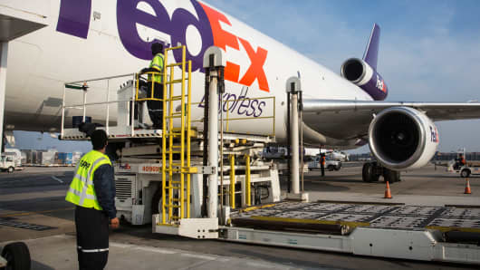 Workers prepare to offload an incoming FedEx plane in Newark, New Jersey.