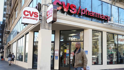 Pedestrians walk by a CVS store in San Francisco.