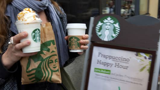A customer holds Starbucks Corp. beverages as she exits one of the company's coffee shop.