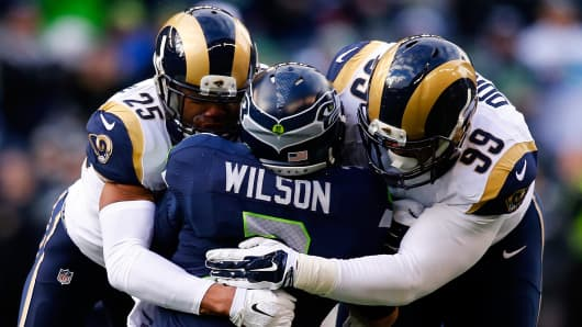 Quarterback Russell Wilson #3 of the Seattle Seahawks is tackled by the St. Louis Rams in a 2014 NFL game.
