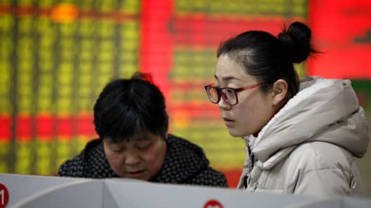 Share holders observe the stock market at a stock exchange corporation on December 17, 2014 in Nantong, Jiangsu province of China.
