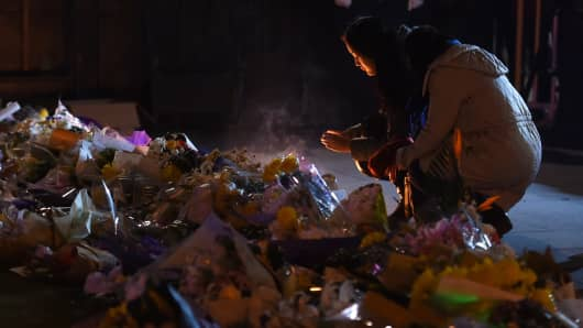 Two women place candles at the site of a New Year's Eve stampede at The Bund in Shanghai.