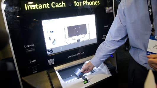 A technology representative demonstrates the ecoATM which purchases used cellphones from consumers during CES.
