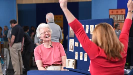 Leila Dunbar, right, celebrates after the $1 million appraisal of rare Boston Red Stockings baseball cards on Antiques Roadshow.