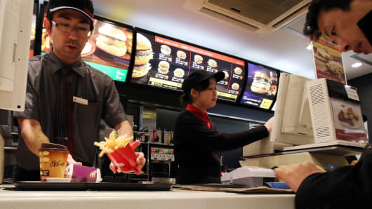 An employee serves french fries to a customer at a McDonald's restaurant in Tokyo.